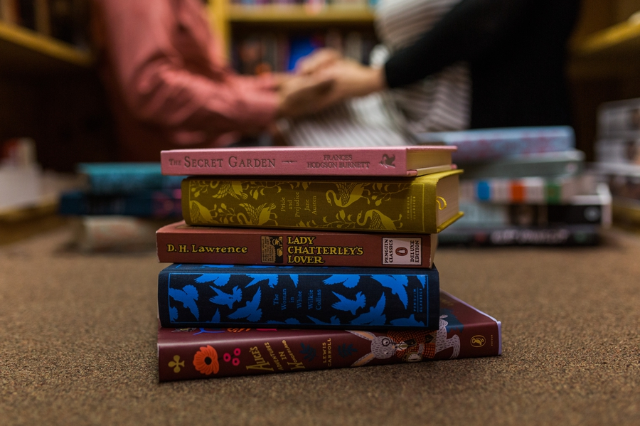 stack of books with engaged couple holding hands in background