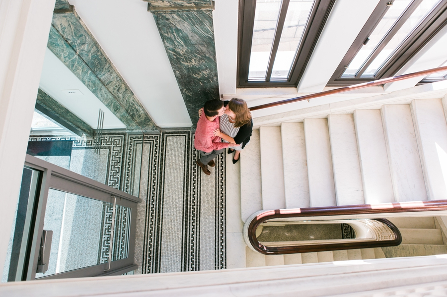 engaged couple kissing on stairs of Columbus Metropolitan Library Engagement