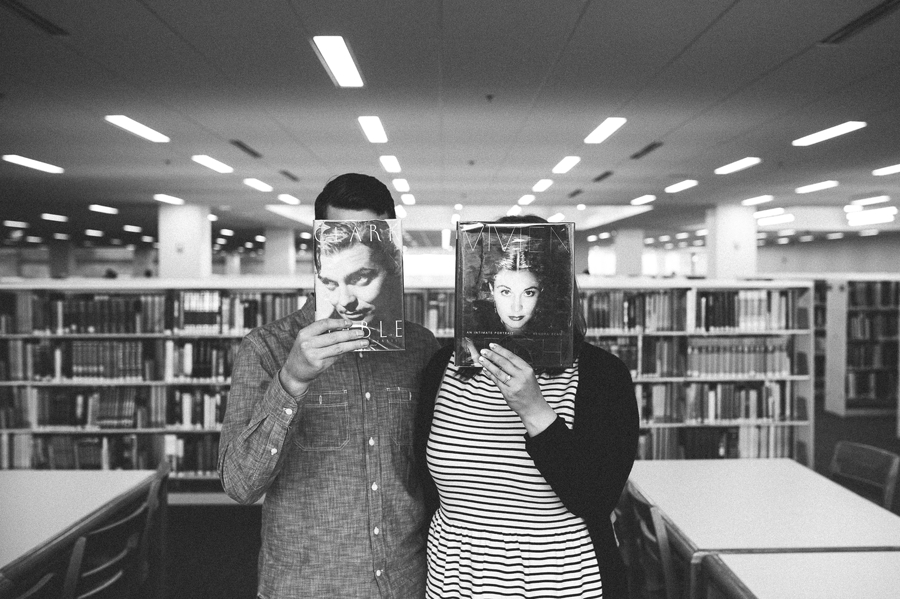 engaged couple holding books over faces at Columbus Metropolitan Library Engagement