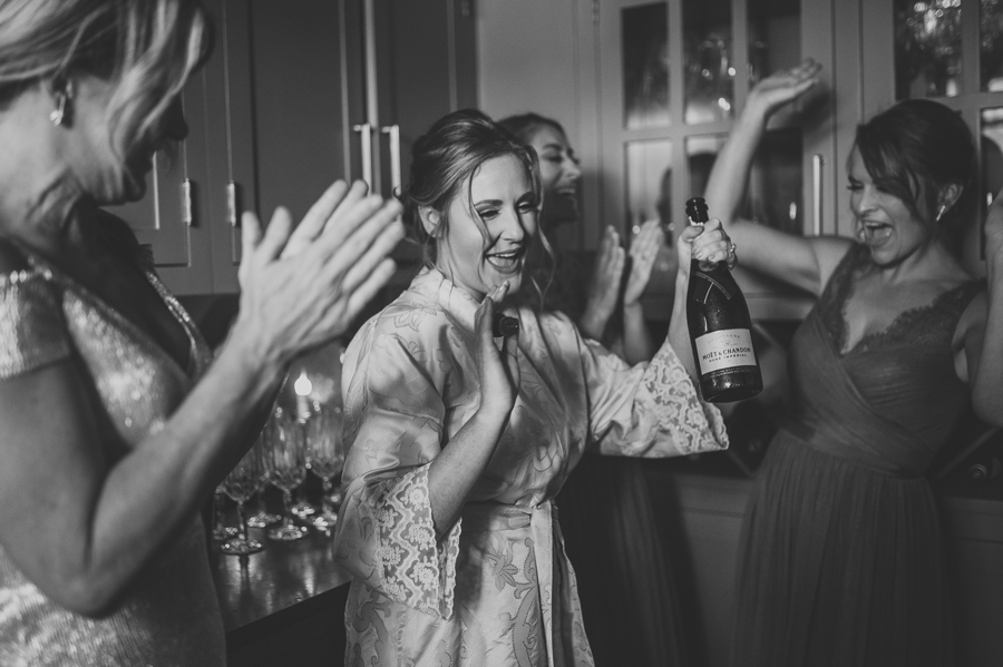 black and white photo of bride opening champagne bottle