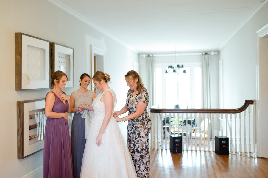 bride holding hands wiith bridesmaids while getting into gown