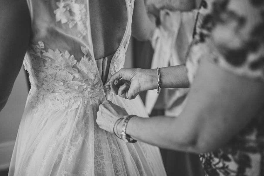 close up photo of bride getting dress zipped up