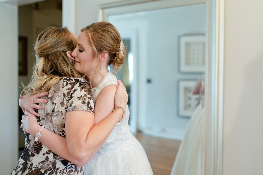 bride hugging her mom after she opens gift