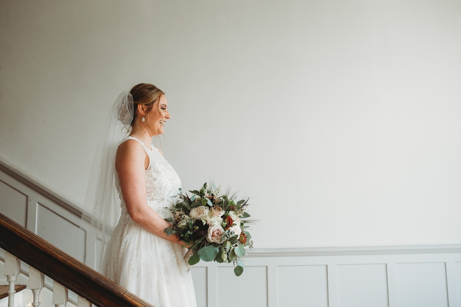 bride waiting for first look on stairs