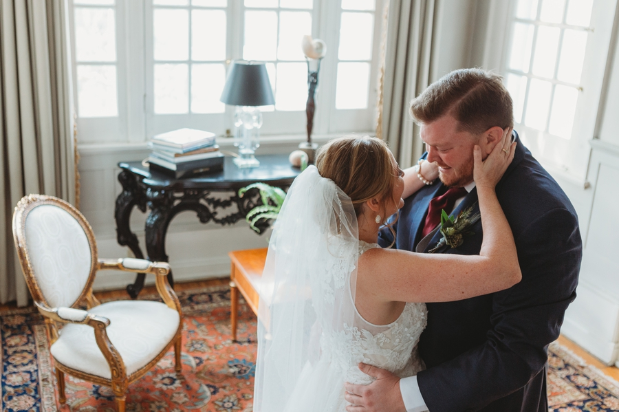 bride touching grooms face during first look