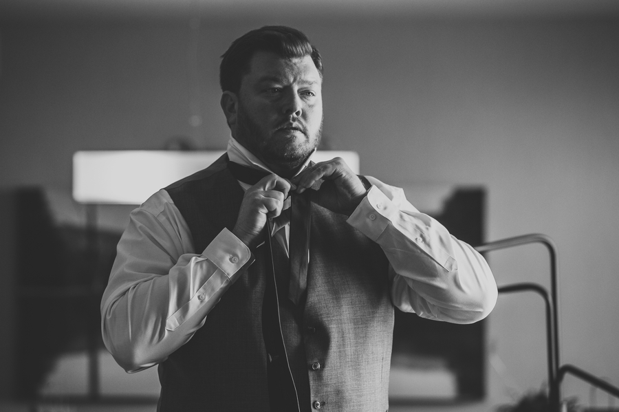 black and white photo of groom putting on tie