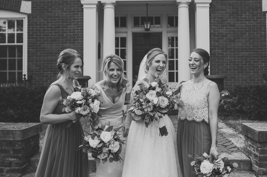 black and white photo of bridesmaids laughing with bride at grange insurance audubon center wedding