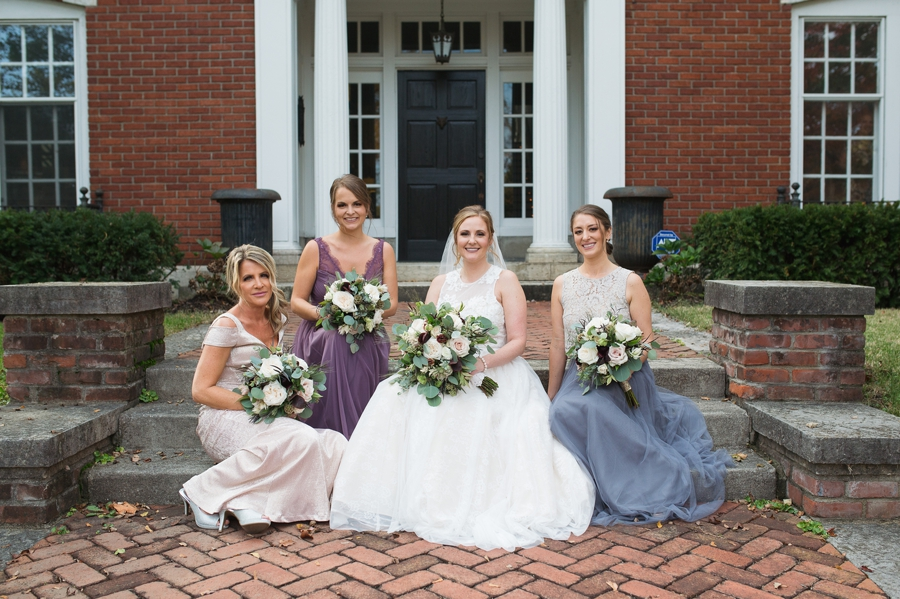bridesmaids and bride sitting on brick steps