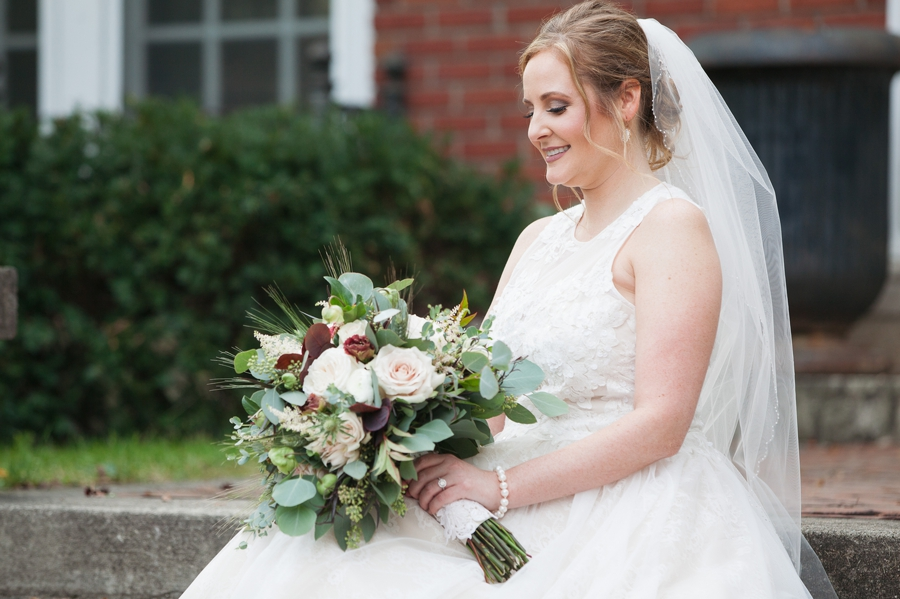 bride looking down at bouquet while sitting