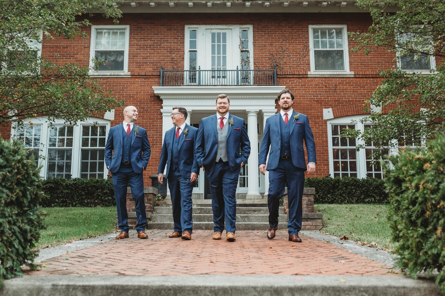 groomsmen walking in front of victorian home