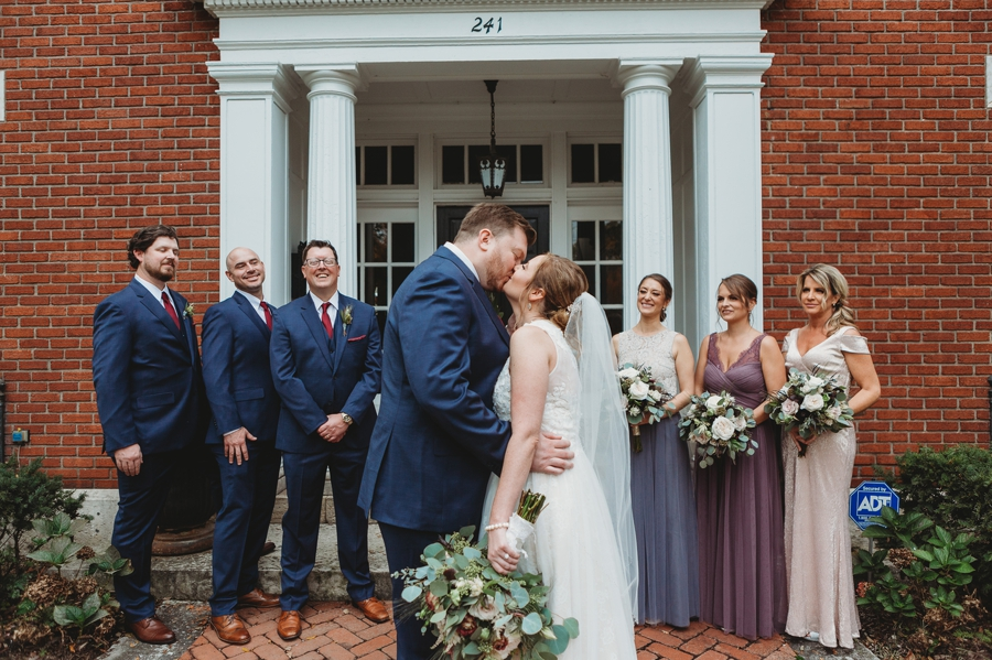 bride and groom kissing with wedding party