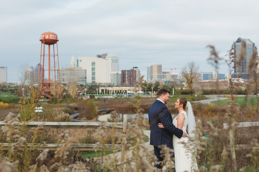 bride and groom with columbus skyline at grange insurance audubon center wedding