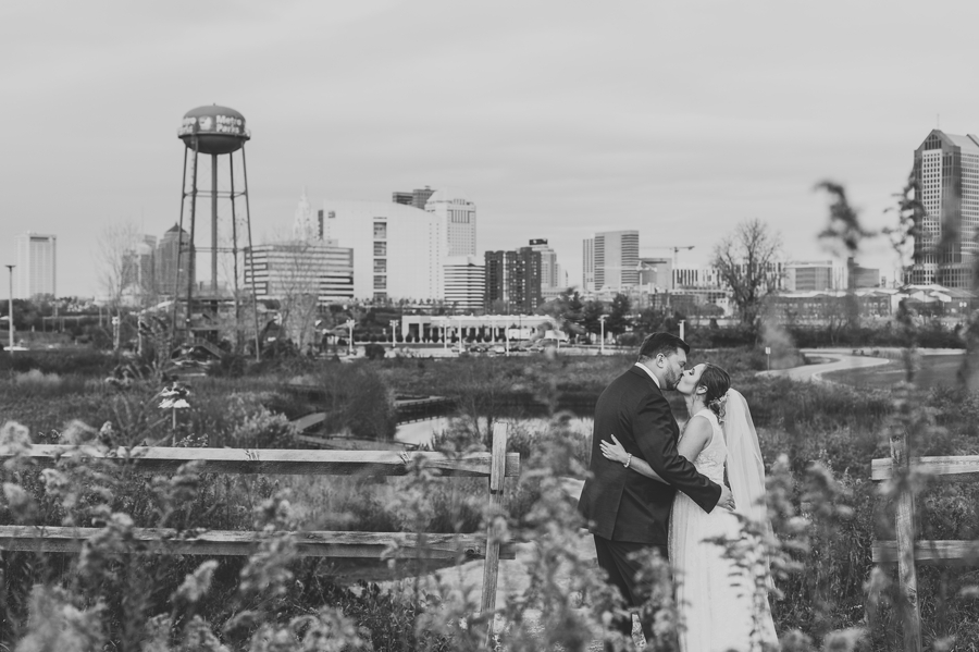 black and white photo of couple kissing with columbus skyline at grange audubon