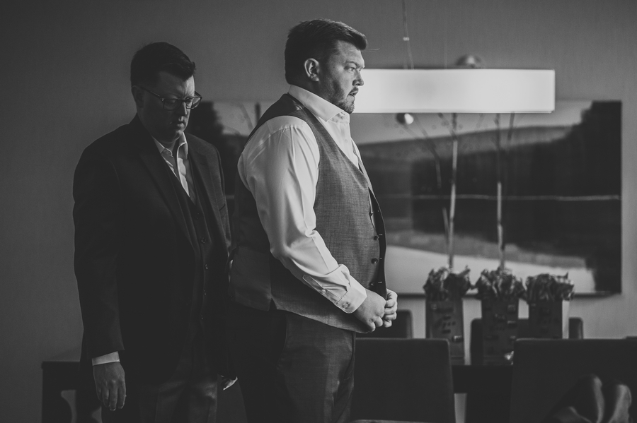 black and white photo of groom putting on vest