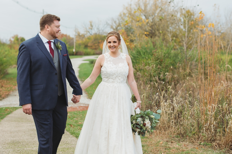 bride leading groom on a walk while holding hands