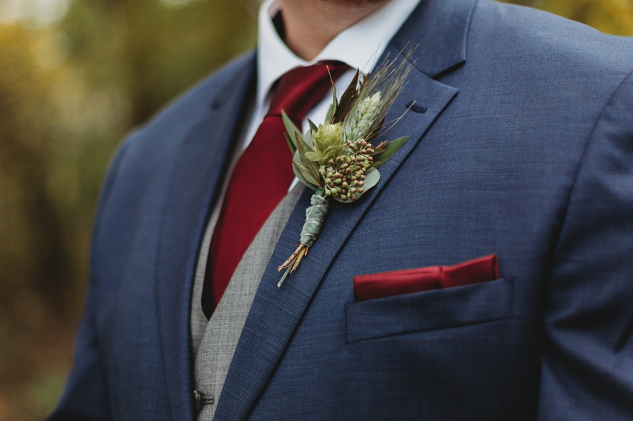close up of grooms green boutonniere