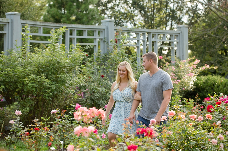 engaged couple walking in rose path at Inniswood Metro Gardens