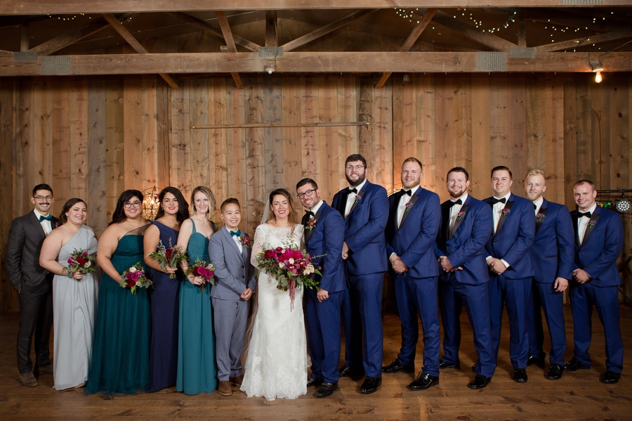 wide photo of wedding party with bride and groom inside jorgensen farm