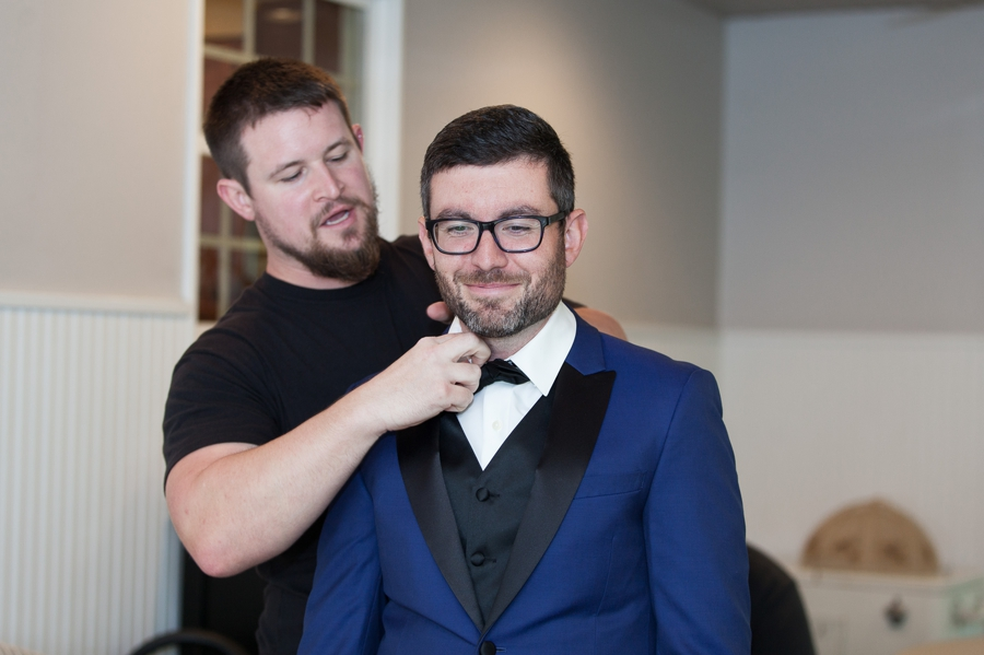 groom getting bow tie adjusted by best man