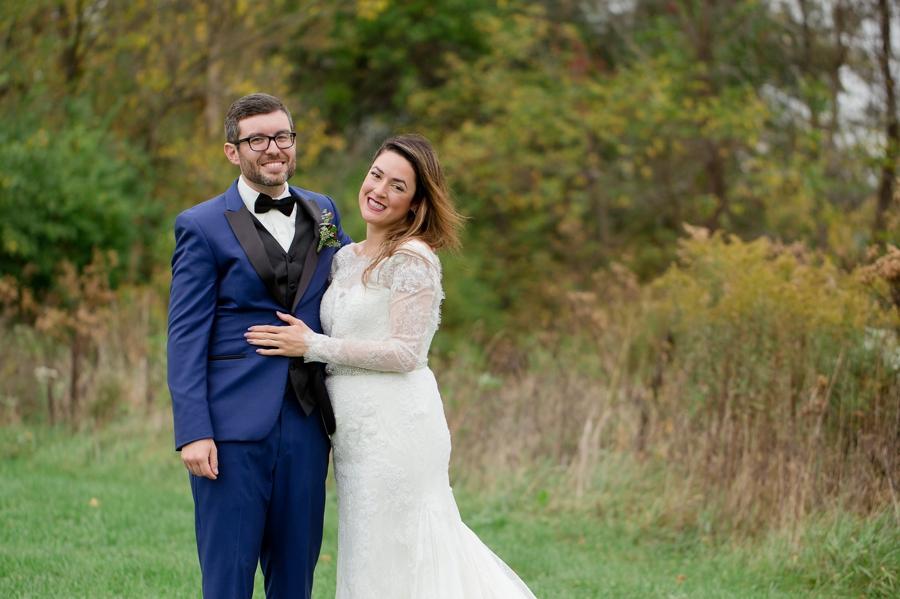 bride and groom in field smiling at jorgensen farm