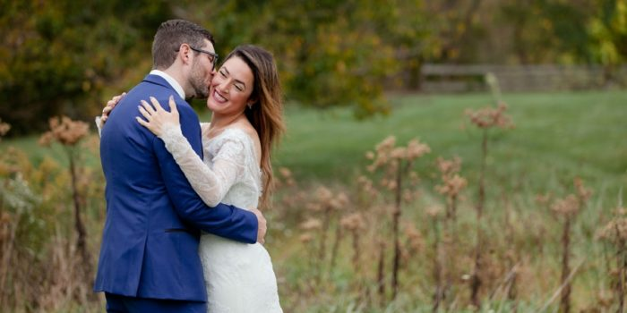 groom kissing brides cheek in field at jorgensen farm wedding
