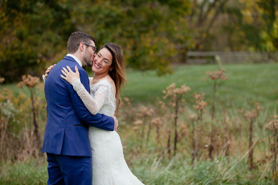 groom kissing brides cheek in field at jorgensen farm wedding