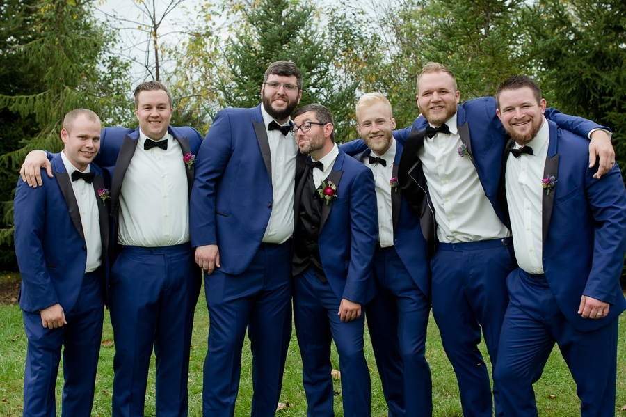 groom and groomsmen laughing with arms around each other
