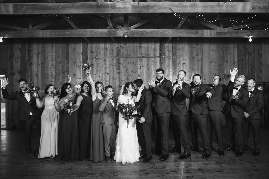 black and white photo of wedding party cheering on couple at jorgensen farm