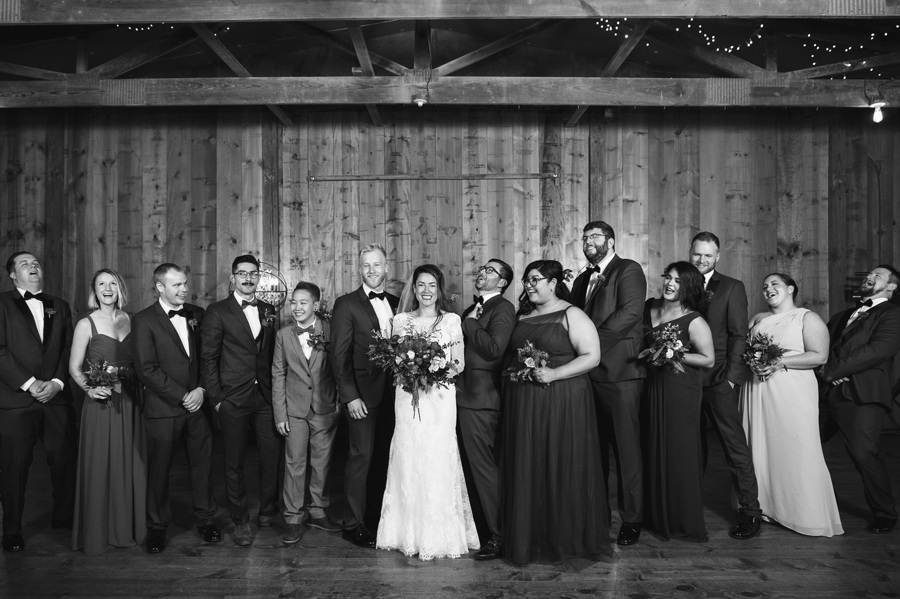 black and white photo of wedding party laughing
