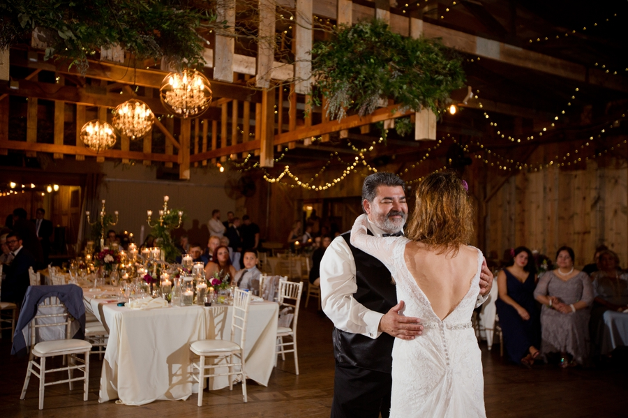 father of bride smiling at bride during dance