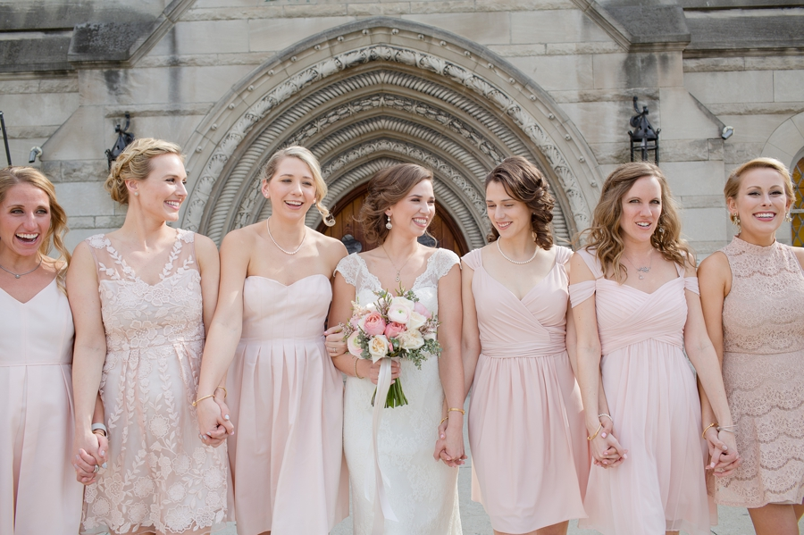 bride and bridemaids holding hands walking at the bluestone