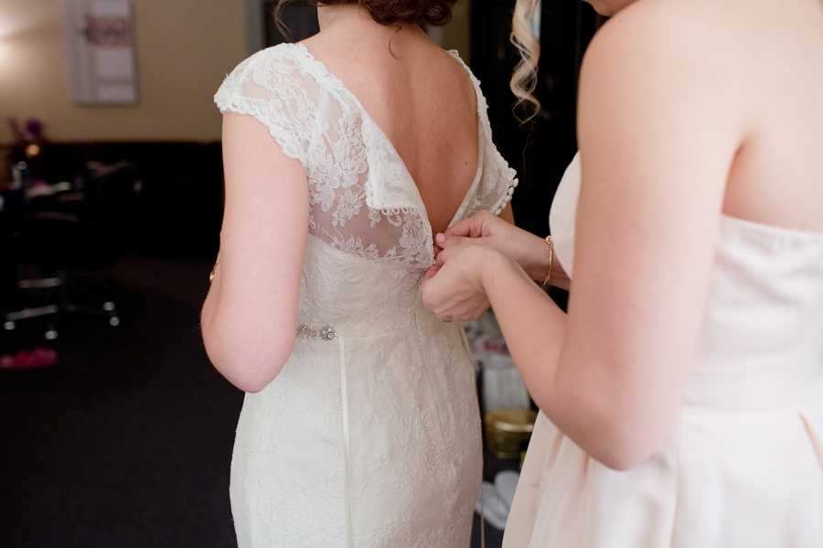 brides sister zipping up brides gown at the bluestone