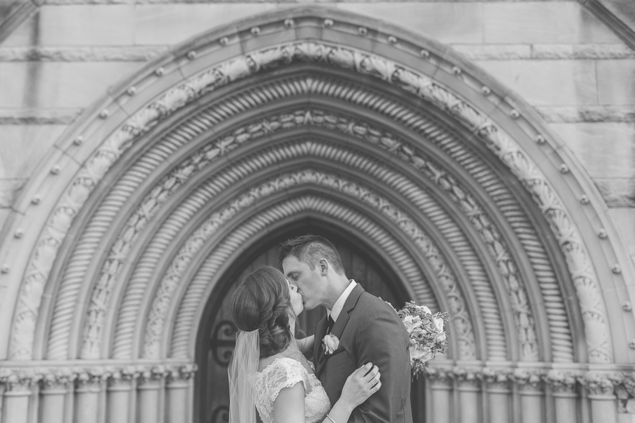 bride and groom kissing outside of the bluestone entrance