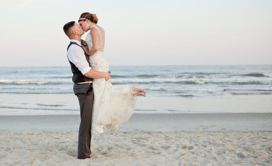 groom holding bride up while kissing on ocean isle beach