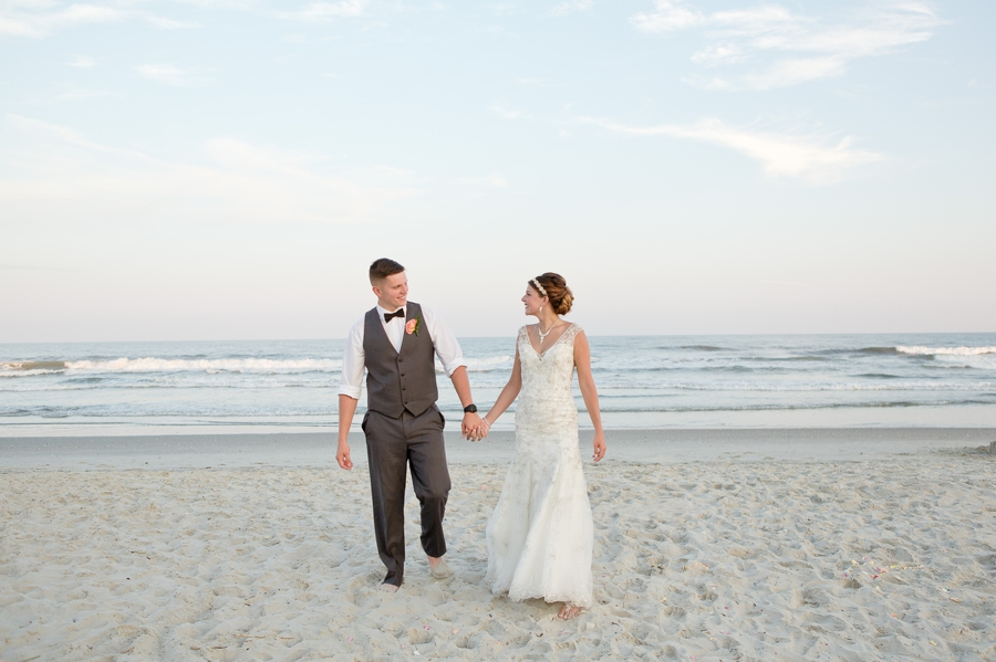 bride and groom walking while looking at each other on beach