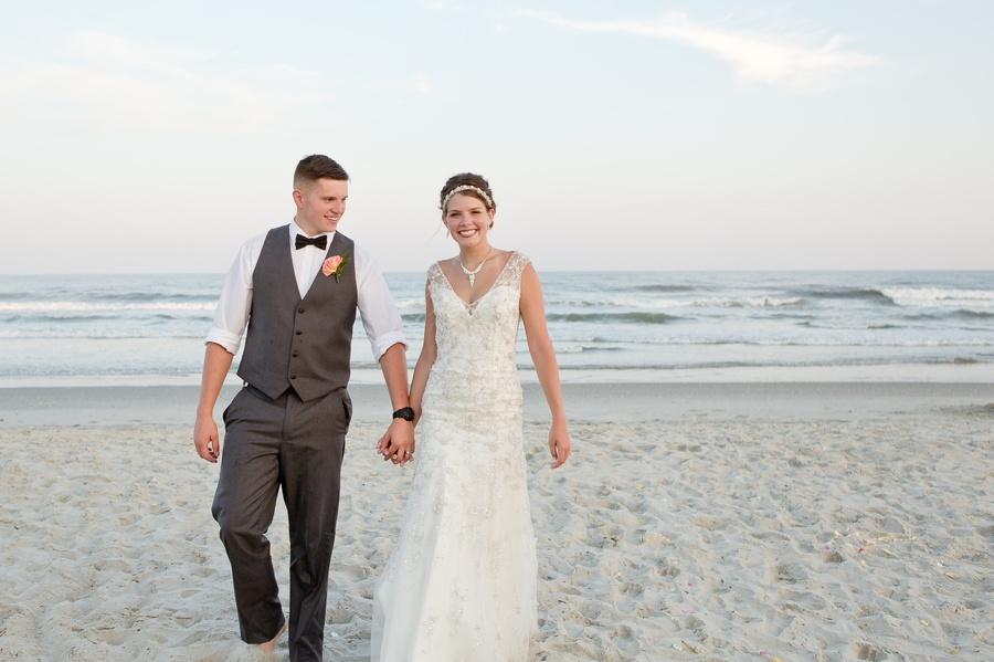 bride and groom walking on beach smiling
