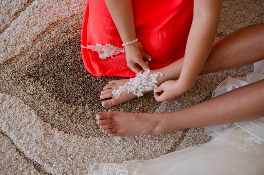 bridemaids putting on brides lace barefoot sandals