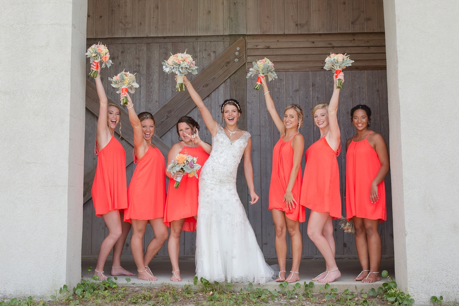 bride and bridesmaids with bouquets in air