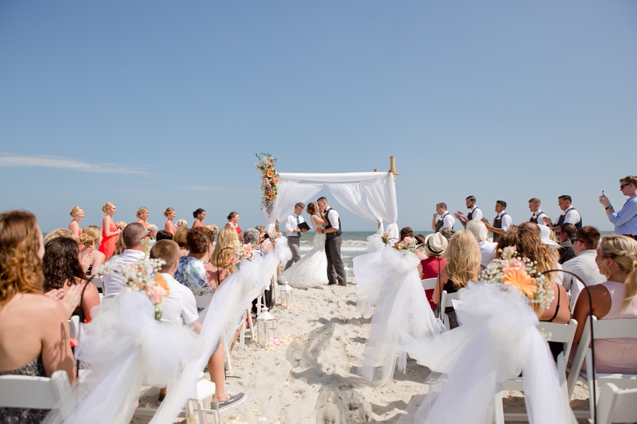 first kiss of bride and groom at ocean isle beach wedding