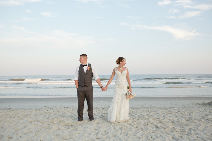 bride and groom looking opposite directions on beach