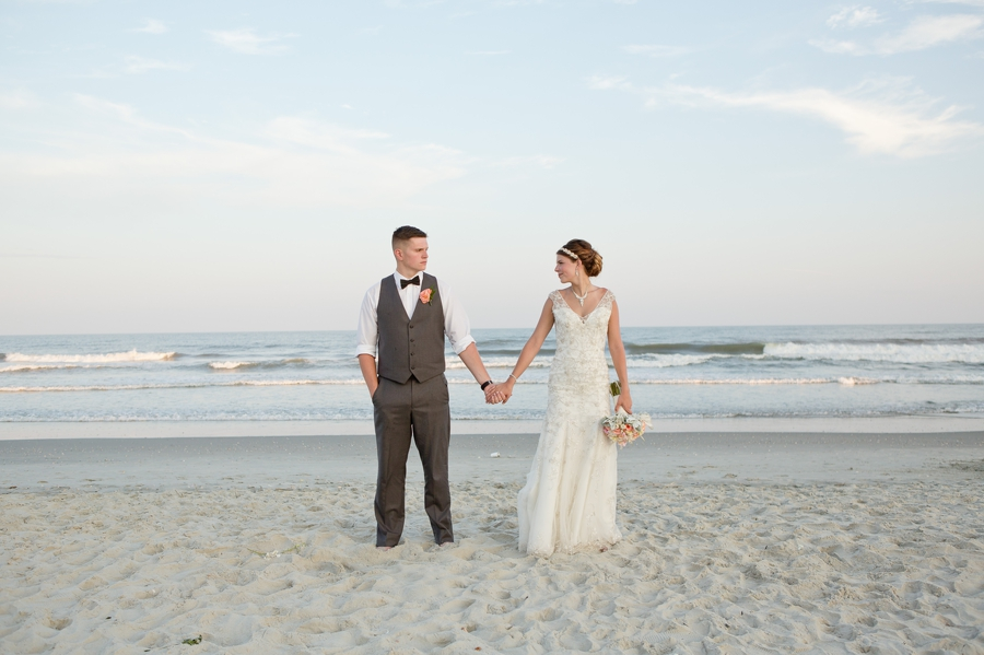 bride and groom looking at each other on beach of ocean isle