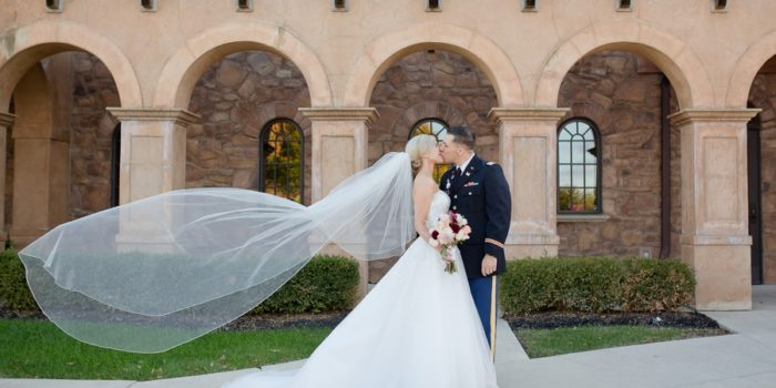 married couple kissing with veil flying in air