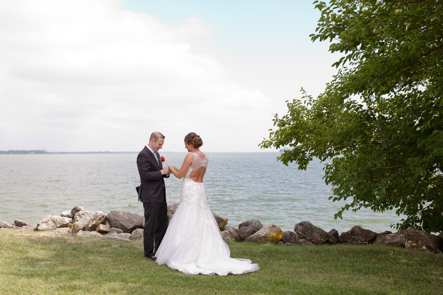 waterfront photo of bride and groom holding hands