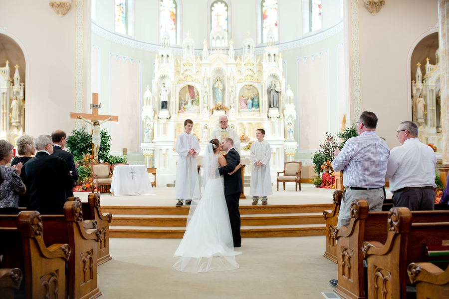 bride and groom first kiss at immaculate conception church
