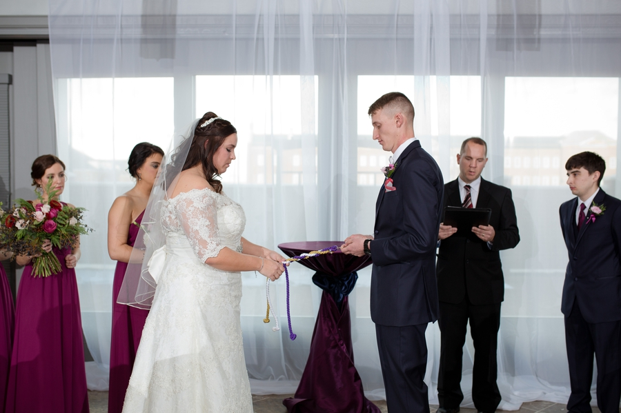 bride and groom tying knot at wedding ceremony