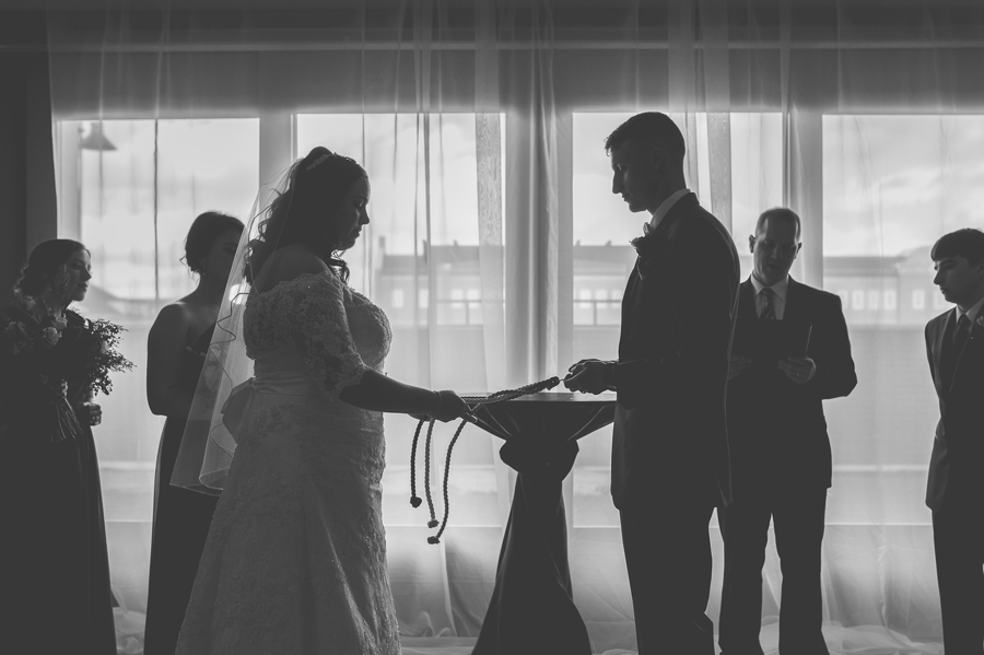 black and white photo of bride and groom tying wedding rope