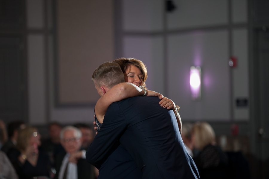 mother of son hugging groom during dance