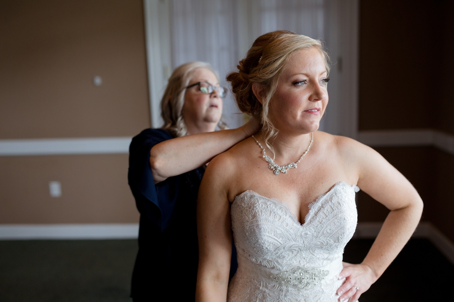 mother of bride putting on brides necklace