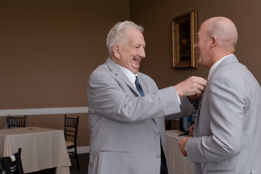 father of groom helping groom get dressed