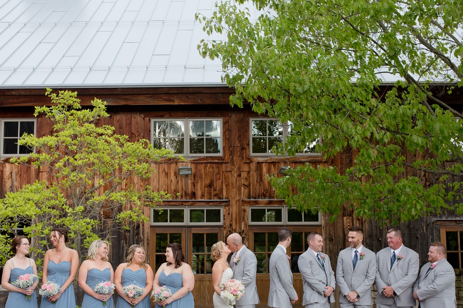 wedding party photo with couple kissing